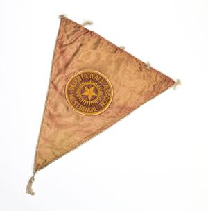 A triangular flag, a circle seen in the middle with the words Indian Football on it, a star in the middle. There's a tassle attached to the tip of it.
