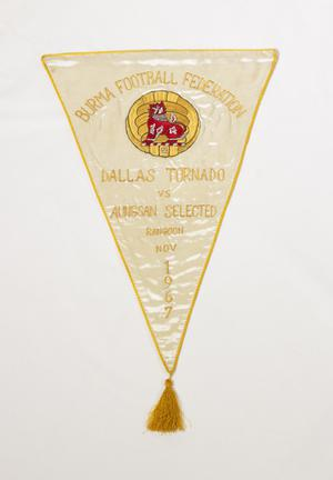 A triangular flag, white in color and yellow outline. At the top it says Burma Football Federation, under it is a gold and red color. The tip of it has a tassle hanging from it.