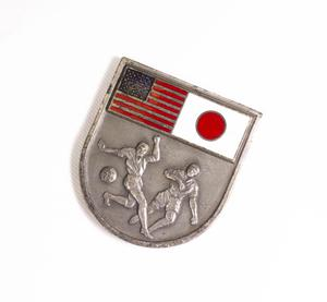 A silver medal, the bottom half of it an outline of two men and a soccer ball. The top of it has the American flag in the top left, the right top a white flag with a red circle in the middle of it.