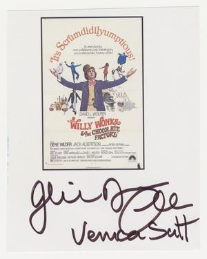 A small white piece of paper with the promotional image for the film Willy Wonka and the Choclate Factory, showing a man in purple suit jacket and yellow top hat with arms wide, and small images of children, oompa loompas, and a ferry boat around him. The words It's Scrumdidilyumptions! arch above him from hand to hand. The film information is below, and a dark rectangle surounds the image and information. Beneath the rectangle is a signature in black ink.