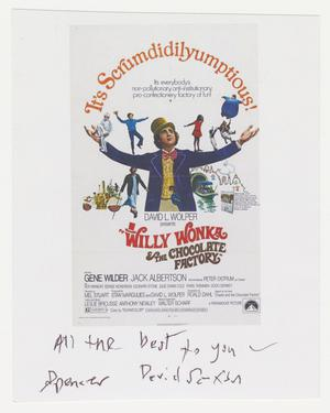 A small white piece of paper with the promotional image for the film Willy Wonka and the Choclate Factory, showing a man in purple suite jacket and yellow top hat with arms wide, and small images of children, oompa loompas, and a ferry boat around him. The words It's Scrumdidilyumptions! arch above him from hand to hand. The film information is below. Beneath the image is a signature in black ink.