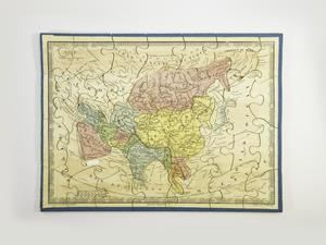 A completed puzzle with a blue border and white background showing a map of Asia with countries colored either blue, yellow, red, orange, or green, and small text throughout.