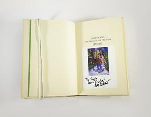 Photograph of a book open to the title page. The left page is plain white paper. The right page has the title, Charlie and the Chocolate Factory, and below is a white piece of paper with a color photograph with a blond boy in a red sweater holding a golden ticket. Below the photo on the card is an inscription in black ink.