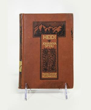 Photograph of the cover of Heidi. The cover is brown with two black boxes in a T shape. The top box has a black line print of a mountain range with solid black pine tree in the foreground. The lower box had the title and author information in gold, with two leafy vines underneath with flowers at the top.