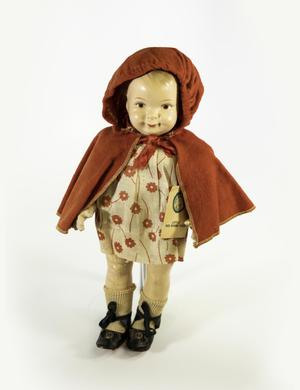 Photograph of a porcelain doll, with a painted face, and painted on blonde hair. She wears a red cape with a hood over her head, and a short white dress with red flowers printed on it. She wears white knit socks and black shoes with buttons on them. Under her cape, she had a tag that said little red riding hood, with a cicular label.
