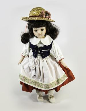Photograph of a porcelain doll with long curled dark hair with bangs, and a woven straw hat with a bunch of pink flowers on one side. The doll wears a dress with white sleeve and collar, a dark blue corset, a red skirt and a white apron with flowers printed along the bottom edge.