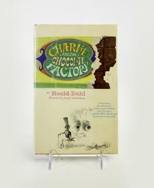 Photograph of the cover of Charlie and the Choclate Factory. Cover shows title in a green oval on the wrapper of a chocolate bar torn open at the right end. Below is a line illustration of a boy's head with his chin resting on his crossed arms, and a small man with a top hat and can sitting on one of the boy's arms. Both figures look at the viewer.