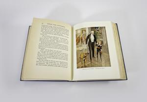 Photograph of an open book with the left page being text and the right page having an illustration. The illustration shows and old man in a tuxedo holding a cane walking through a large room with marble floors. The man is being pulled by the hand by a young boy with long blond hair, wearing a black velvet suit with red belt. A brown dog stands to the left looking back at them.