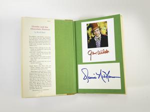 Photograph of a book open to it's end page, covered in green paper. The dust jacket flap covers the left side of the cover and has a column of text. On the right page are two pieces of white paper attached, the top has a photograph of Gene Wilder as Willy Wonka with a purple suite and orange top hat, and his signature below. The lower rectangle of paper has a signature in blue ink.