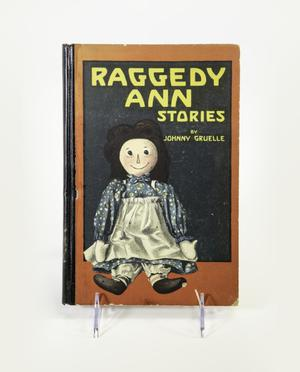 Cover of the book Raggedy Ann Stories, with red border and image of a smiling  doll with a blue floral dress and white apron sitting in front of a black  background.