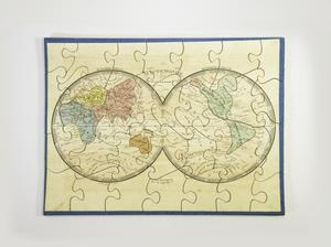 A completed rectangular puzzle with a blue boarded and white background, showing a mappa mundi, or world map in two connected circles, major land masses are blue, red, yellow, orange, and green, with small text throughout.