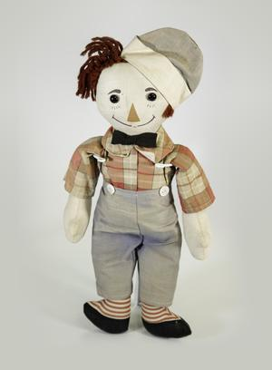 Photograph of Raggedy Andy doll with red plaid long sleeve shirt with collar and black bow tie. He wears faded blue pants with two buttons on either side of the top edge. He wears a cap tilted to one side of his head in the same faded blue fabric. He had black shoe button eyes, a painted triangle nose, a painted smile, and dark red yarn hair.