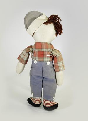 Photograph of back of Raggedy Andy doll with red plaid long sleeve shirt with collar. He wears faded blue pants with two buttons on either side of the top edge. He wears a cap tilted to one side of his head in the same faded blue fabric. He has dark red yarn hair on the top of his head.