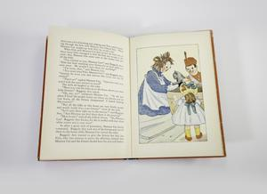 Open book with text on the left page and an illustration on the right page, of a Raggedy Ann doll dressed in a blue floral dress with white apron pulling a grey kitten out of a basket half her height, she is joined by a soldier toy standing behind the basket smiling, and a smaller doll with dress and hat stands in front of the basket with her back visible.