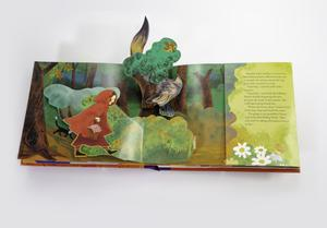 Photograph of an open pop-up book. The pop up illustration shows a girl in a red hood and cape walking through a forest. She pops out from the background forest illustration. Hidden behind a tree and bush, and popping out from the center of the page and the top of the book, is a wold with a grin on his face, looking at the girl. The right side of the right page has a flap with text on it.