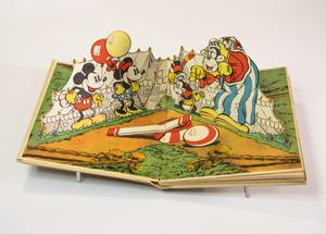 Book laying open showing Mickey and Minnie Mouse holding red and yellow balloons smiling at two other characters wearing clown clothes in front of a large tent.