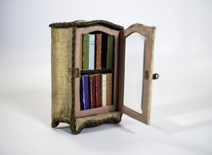 Photography of a small book case filled with 10 miniature books of different colors, the case has a door that is open with a glass front, and the case is covered in slightly discolored white silk and a dark cord around the  edges.
