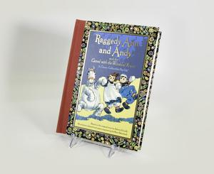 Photograph of the cover of the pop-up book. An illustration in the middle shows a camel stuffed animal, Raggedy Ann in a white apron, and Raggedy Andy in blue pants holding hands and jumping. Around the rectangle illustration is a floral decoration on a black background, with red along the spine of the book.