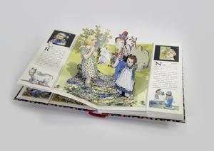 Photograph of an open pop-up book. The page shows a young girl with blonde hair looking at Raggedy Ann and Andy in the foreground with two gamel stuffed animals in the background next to some bushes that all pop up off the page. The edge of either page has a flap with some small illustrations and text.