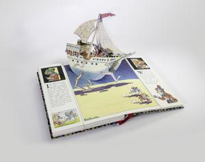 Photograph of an open pop-up book. The page shows a large sailing ship popping us over the top of the page. Where the ship connects with the flat page, 3 mechanical legs are shown with the ship walking through the desert. There are a group of people at the front of the ship, and two camels with figures running in front of the ship.