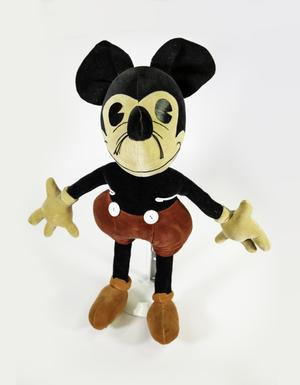 Velvety Mickey Mouse doll with yellowed gloves, red shorts with two large white buttons, and faded orange shoes, eyes are large slightly shiny ovals with triangles cut from the sides, and two string whiskers hang from each side of the nose.