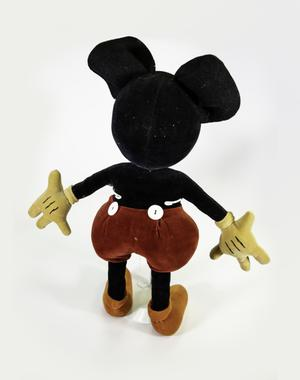 Back of velvety Mickey Mouse doll with yellowed gloves that have three black stripes of thread, red shorts with two large white buttons, and faded orange shoes.