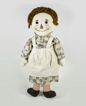 Photograph of a Raggedy Ann doll with a grey floral dress, white apron, red striped socks, and dark shoes, her eyes are black solid buttons and her nose is a red triangle outlined in black, her hair is a dark reddish brown yarn.