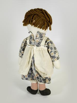 Photograph of the back of a Raggedy Ann doll with a grey floral dress, white apron with a single button holding it closed in the back, red striped socks, and dark shoes, her hair is a dark reddish brown yarn.