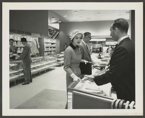 Black and white photograph of store interior. In the foreground a white woman points to something in a display case while talking to a white salesman in a dark suit. The opposite wall of the room has a long display case and a wall of items on shelves behind the case. A white man in a suit talks to a white salesman at the back display case.