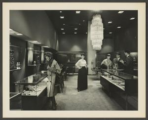 Black and white photograph of a store with glass display cases and a large chandelier hanging from the ceiling. A white woman looks at a display case on the left, a white salesman talks to a white couple at a display case on the right. At the center is a white model standing with hands on hips.