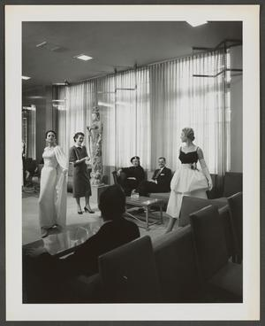 Black and white photograph of two white models posing, wearing fancy dresses. They stand in a seating area of a room with floor to ceiling windows and curtains. People sitting around the edges of the room look at the models, while another white woman stands behind them.