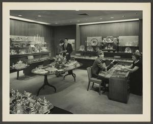 Black and white photograph of a room with shelves lining the walls, and a large display table at the center. All surfaces hold silver items like tea sets and serving trays. A white man and woman stand together behind the large display table, while a white woman sits at display case on the right talking to a white saleswoman.