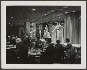 Black and white photo of people sitting at dining tables, wearing suits, nice dresses and hats. They look up and back at three white models on a runway behind the tables.  The models from left to right wear a swimsuit and large hat, a long a-line dress, and a flowing dress with long wrap around head and shoulders that flows to the ground.