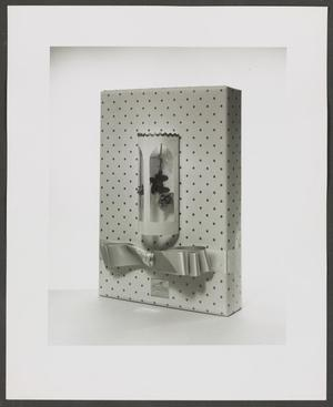 Black and white photograph of a package wrapped in polka dot paper, with a bow on the lower half. Above the bow is a cylinder with large cut outs that show paper flowers hanging upside down.