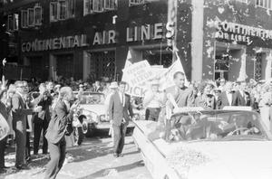 Black and white photo of Richard and Pat Nixon sitting in the back of a white convertable. People fill the streets around them, with some people behind the car holding large signs, one reads Texans for Nixon. Confetti falls from the sky. The building behind them has a sign reading Continental Air Lines.