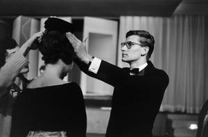 Black and white photo of white man in a tuxedo and glasses adjusting the hat of a woman whose back is turned to the camera.