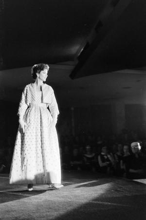 Black and white photo of white model on runway, wearing a long white dress with polka dots and a small matching polka dot jacket. She is heavily lit, while seated audience members can be seen to the right in shadow.