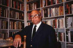 Color photograph of Thomas Tolbert standing in front of two large book cases. He rests one arm over the back of a chair.