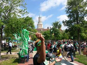 Color photograph of an event outdoors. In the foreground, a person waves a pom-pom, covering their face, while a large cowd of people mingle in the background. A large building with a clock tower stands behind the crowd.