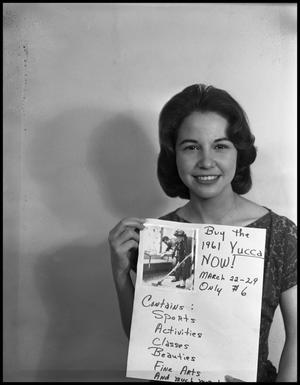 Black and white photo of a woman with short dark hair posing while holding a sign with a photograph on it. The sign says Buy the 1961 Yucca Now.