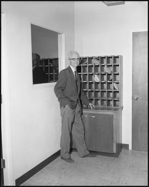 Primary view of object titled '[Professor Dr. L.F. Connell Posing Next to a Wooden Mail Sorter]'.