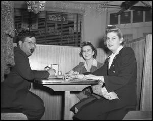 Primary view of object titled '[Three people sit in a restaurant]'.
