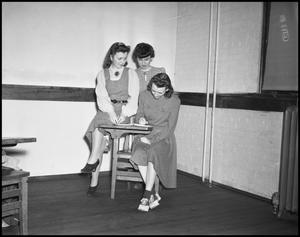 Primary view of object titled '[Three women gather around a desk]'.