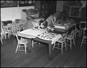 Primary view of object titled '[Girls coloring at a table]'.