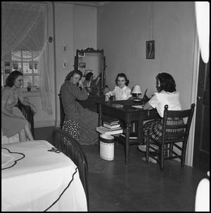 Primary view of object titled '[Four women relaxing in a bedroom]'.