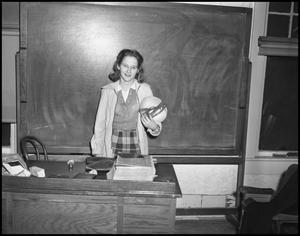 Primary view of object titled '[Woman stands in front of blackboard]'.