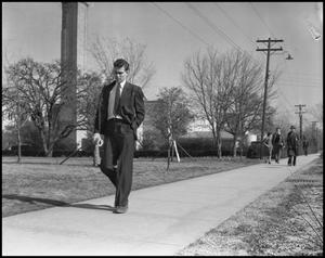 Primary view of object titled '[Man Walking Down Sidewalk]'.
