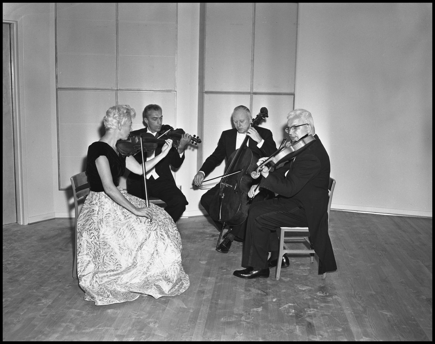 [String Quartet], Photograph of a string quartet. The musicians have been identified as NTSU School of Music faculty members Marjorie Fulton, Russell Miller, Alan Richardson, and George Morey. Aside from the musicians, the room appears empty.,