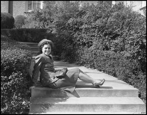 Primary view of object titled '[Woman sitting on the stairs next to hedges]'.