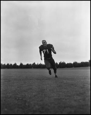 Primary view of object titled '[Football Player No. 71 Running on a Field, September 1962]'.
